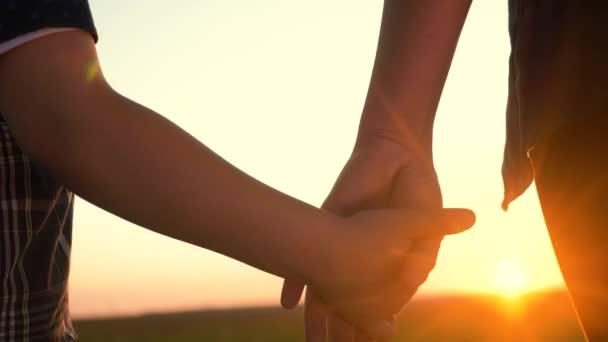 Glückliche Familienmütter und -söhne halten Händchen in Teamarbeit. Mutter und Junge Hand in Hand bei Sonnenuntergang. Eltern Mädchen und Kind glückliche Kindheit. Konzept zum Muttertag