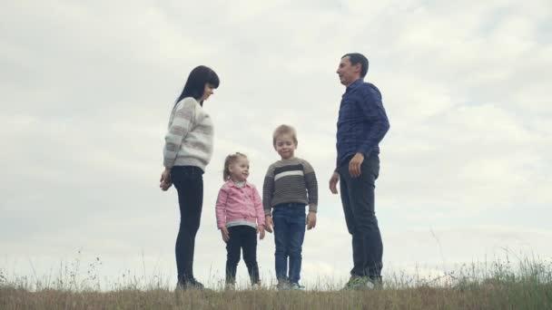 Šťastná rodina. Týmová práce Dospělí rodiče a malé děti ukazuje dům a symbol pohodlí. šťastná rodina maminka táta a děti životní styl vyobrazení domu střecha držet ruce nad hlavou