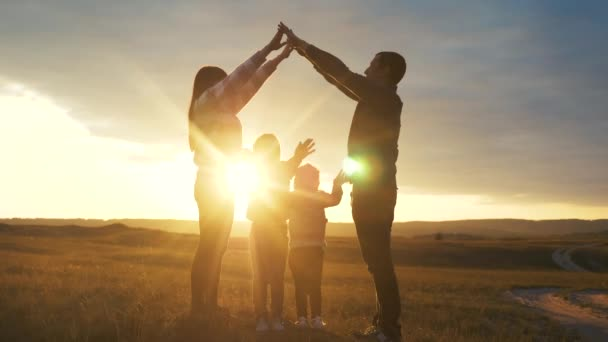 happy family. teamwork adult parents and small children shows a house and comfort symbol silhouette at sunset. happy family mom dad and lifestyle kids children portray a house roof hold their hands