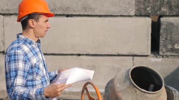 male architect a builds foundation of cement and concrete mixer. concept building constructing architect slow motion video. man builder study with the house paper plan. architect working on