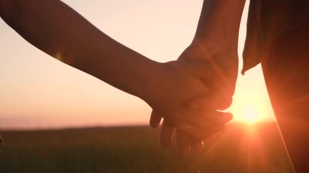 Glückliche Familienmütter und -söhne halten Händchen in Teamarbeit. Mutter und Junge Hand in Hand bei Sonnenuntergang. Eltern Mädchen und Kind glückliche Kindheit. glücklicher Lebensstil Familie Muttertagskonzept