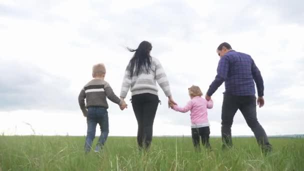 Šťastná rodina. Máma táta a malé děti procházka v parku týmová práce venku drží za ruce. žena muž a životní styl malý chlapec a dívka kráčející na zeleném poli při západu slunce