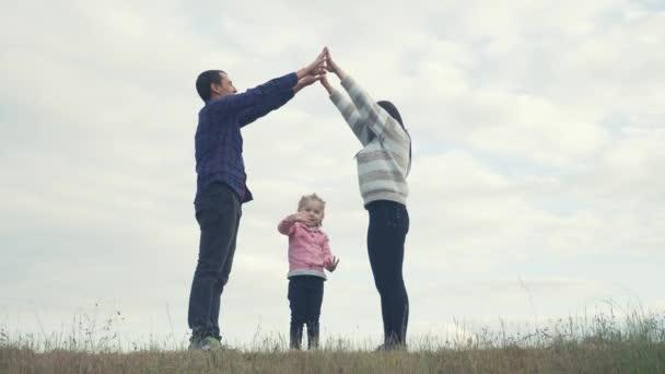 glückliche Familie. Teamwork erwachsene Eltern und kleine Kinder zeigt ein Haus Lebensstil und Komfort Symbol. glückliche Familie Mama Papa und Kinder stellen ein Hausdach dar, halten die Hände über dem Kopf