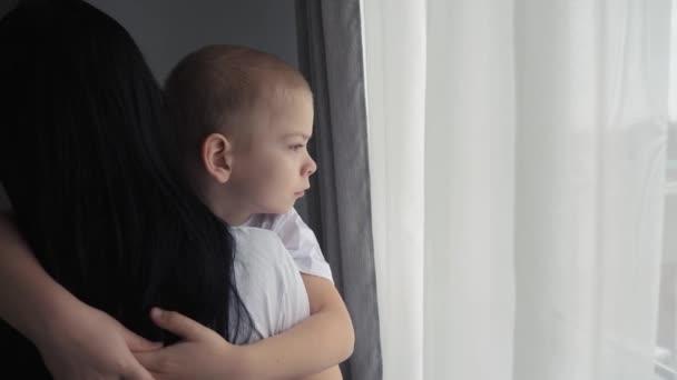 Máma drží svého syna v náručí. šťastný rodinný koncept. Máma drží malého chlapce v náručí při pohledu z okna vnitřní životní styl péče o dítě šťastná rodina