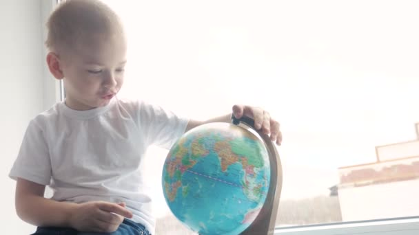 boy studies globe. education travel tourism concept. child twists the globe sits on a window sill. kid looking for a country on a globe map. world map geography lifestyle study