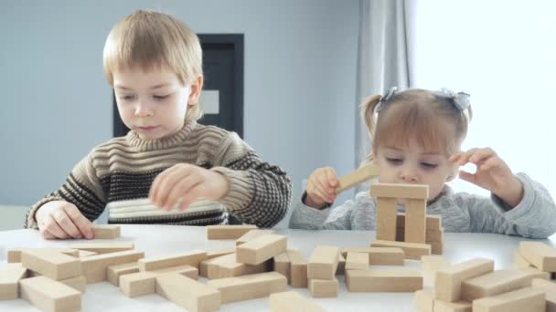 children a play in designer wooden sticks teamwork. happy family kids little boy and girl play in wooden blocks cubes build lifestyle house. brother and sister collect designer development of fine