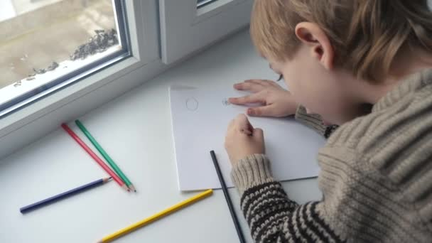 little boy draws with pencils. development of fine motor skills and creativity of imagination in children. kid draws lifestyle by the window on the windowsill