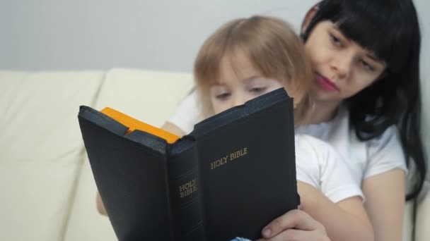 mom daughter read the bible. religion concept holy book believers. lifestyle little girl daughter and mom read the bible