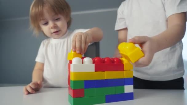 glückliche Familie Junge und Mädchen ein Sammler Konstrukteur drinnen Teamwork. Kinder spielen Spielzeug Konzept. Kinder spielen Bruder und Schwester sammeln Haus von Bauunternehmer