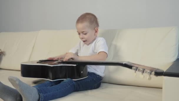the boy lounges, plays the acoustic guitar. kid makes music play and indulge. child is having fun knocking on an acoustic guitar while lifestyle sitting on a sofa