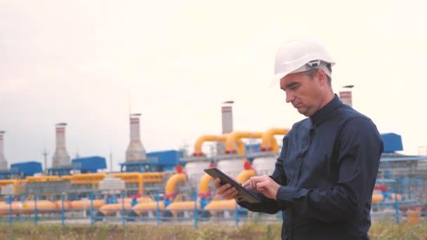 Konzept für die Förderung von Erdöl und Erdgas im Bergbau. Ingenieurskraft und Energie mittels digitaler Tablets. Arbeiter mit Helm bei Arbeiten in einer Ölgasanlage. Ingenieur studiert Lebensstil dokumentiert Wirtschaftsbranche