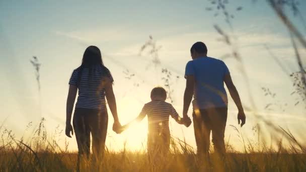 boldog család és a gyerek együtt szórakoztató séta naplementekor a parkban a természetben. Anya apa és fiú sétálni szabadtéri életmód a parkban naplemente sziluett. A szülők és a gyerekek együtt sétálnak. emberek a
