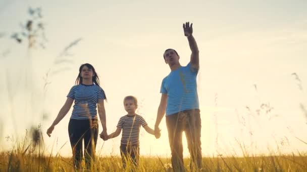 happy family and kid together fun walk at sunset in the park in nature. mom dad and boy son walk lifestyle outdoor in the park sunset silhouette. parents and child together are walking. people in the