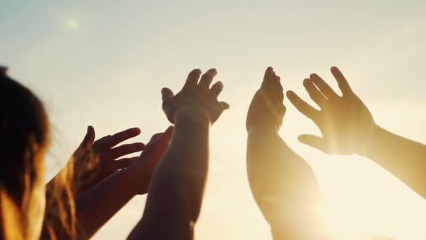 boldog család emberek csoport húzza a kezét a nap csapatmunka. sziluett emberek party tánc rekreációs ünnep. Az emberek egy zenei koncerten felemelik a kezüket. vallás fogalom életmód napfény