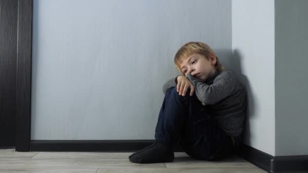 sad upset boy sitting in corner. Child lifestyle punished sitting crying in the corner. Domestic violence concept. Child abuse