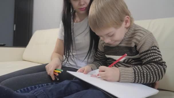 A kisfiúk és az anyák rajzolnak csapatmunkát boldog családi koncepció. gyerek gyermek fia anyával egy nő részt vesz ceruza rajz életmód. lecke a gyermekek kreativitásának fejlesztéséről