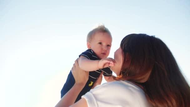 Máma zvrací malého syna, jak si hraje v parku. Den matek dítě snít dětství šťastný rodinný koncept. Maminka si hraje s malým synem na sluníčku. lidé v parku životní styl šťastný rodina