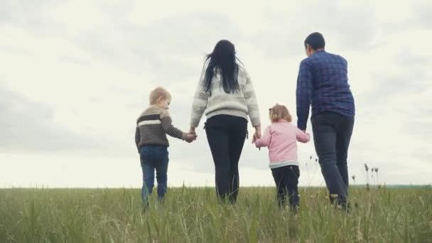 Šťastná rodina. Máma táta a malé děti procházka v parku týmová práce venku drží za ruce. žena muž a malý chlapec a dívka kráčející na zeleném poli při západu slunce životní styl