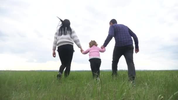 Šťastná rodina. Máma táta a malé dítě běží v parku zvednout ruce hrát týmovou práci venku držet se za ruce. žena muž a holčička zvednout ruce na zelené louce při západu slunce