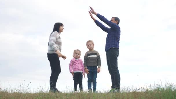 Šťastná rodina. Týmová práce Dospělí rodiče a malé děti ukazuje dům a symbol pohodlí. šťastný rodina maminka táta a děti děti vykreslit dům střecha držet ruce nad životním stylem jejich hlavy