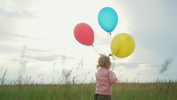 daughter little girl fun runs with balloons a on her birthday outdoors by field. dream happy family concept. child girl kid day. child is lifestyle running and balloons on a background of blue sky
