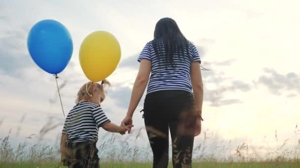 Menschen im Park. glückliche Familie Tochter und Mutter spazieren im Park mit Luftballons Silhouette Teamwork Geburtstagsparty bei Sonnenuntergang. Das Konzept einer glücklichen Familie, die zusammenlebt. glückliche Familie