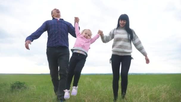 Šťastná rodina. Máma táta a malé dítě běží v parku zvednout ruce hrát týmovou práci venku drží ruce životní styl. žena muž a holčička zvednout ruce na zelené louce při západu slunce