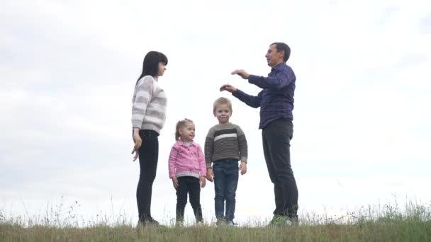 Šťastná rodina. Týmová práce Dospělí rodiče a malé děti ukazuje dům a symbol pohodlí. šťastný rodina maminka táta a děti životní styl děti vykreslit dům střecha držet ruce nad hlavou