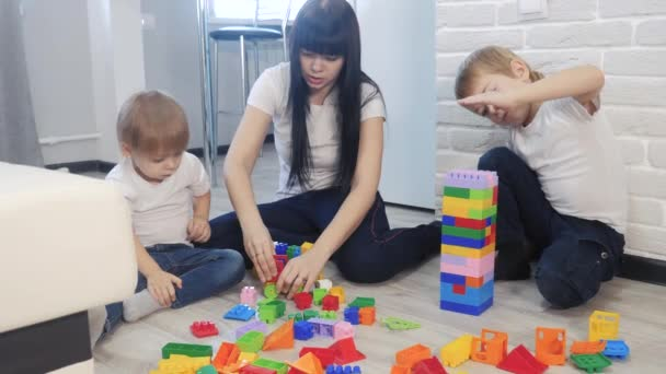 childhood happy family mom and children are playing concept little girl and boy brother and sister collects constructor teamwork. child plays toys sitting on floor. children play in a lifestyle team