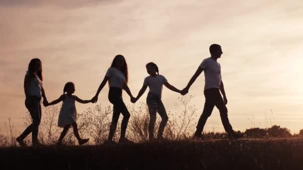 boldog család sziluett naplementekor séta a parkban. gyermekkori álom koncepció. boldog család együtt sétálnak a természetben. barátságos családi álom séta a parkban naplemente napfény életmód