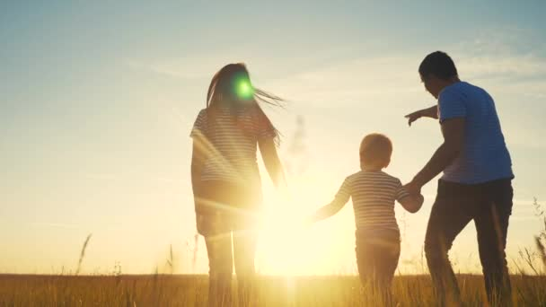 happy family and kid together fun walk at sunset in the park in nature. mom dad and boy son walk outdoor in the park sunset silhouette. parents and child together are walking. people lifestyle in the