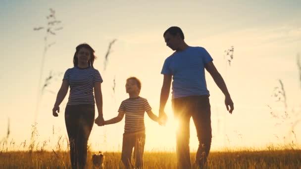 šťastná rodina a děti spolu zábavná procházka při západu slunce v parku v přírodě. Máma táta a kluk životní styl syn chodit venku v parku silueta západ slunce. rodiče a dítě spolu chodí. lidé v