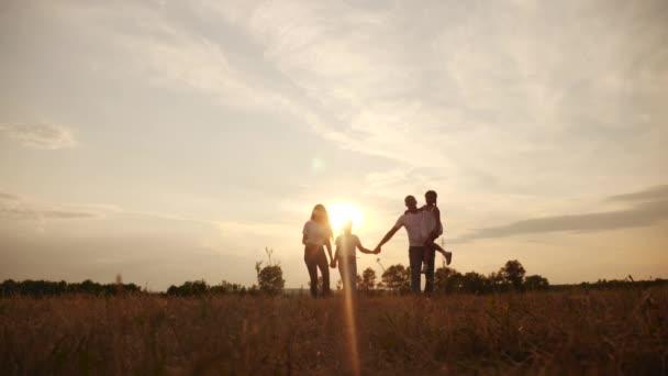 šťastné rodinné děti se společně procházejí v parku při západu slunce silueta. lidé v konceptu parku máma táta dcera životní styl a sestra radostná procházka. rodiče a malé dítě zábava léto
