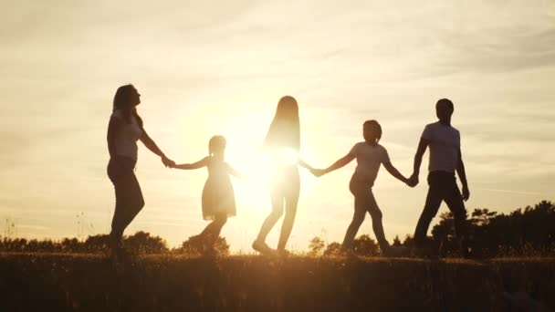 happy family silhouette at sunset walk in the park. childhood dream concept. happy family walking together in nature outside. friendly family dream walk in lifestyle the park at sunset sunlight