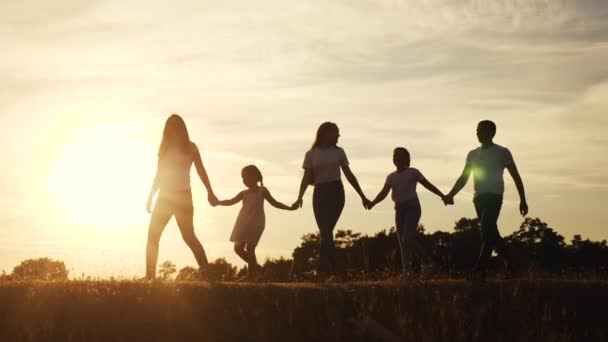 glückliche Familiensilhouette bei Sonnenuntergang Spaziergang im Park. Kindheitstraum. glückliche Familie, die zusammen in der Natur draußen spazieren geht. Familienfreundlicher Traumspaziergang im Park bei Sonnenuntergang