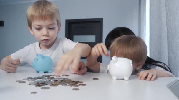 Šťastná rodina šetří peníze. Máma a děti dávají peníze do banky pro prasata. holčička a chlapec dát mince v prasátko banky