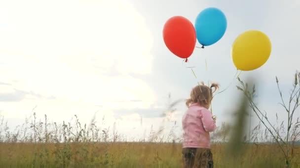 dcera holčička zábava běží s balónky a na její narozeniny venku na poli. snít šťastný rodinný koncept. Den dětského života pro děti. dítě běží a balónky na pozadí modré oblohy
