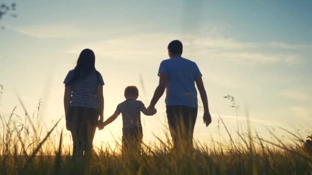 boldog család és a gyerek együtt szórakoztató séta naplementekor a parkban a természetben. Anya apa és fia sétálnak kint a parkban naplemente sziluett. A szülők és a gyerekek együtt sétálnak. emberek a parkban