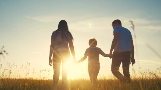 šťastná rodina a děti spolu zábavná procházka při západu slunce v parku v přírodě. Máma táta a kluk syn chodit venku v parku životní styl západ slunce silueta. rodiče a dítě spolu chodí. lidé v