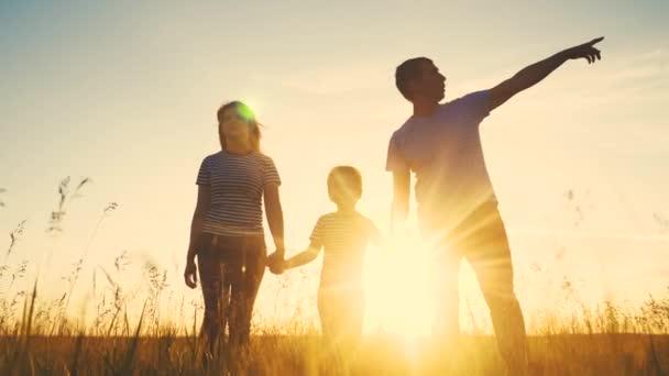 boldog család és a gyerek együtt szórakoztató séta naplementekor a parkban a természetben. életmód anya apa és fiú sétálni szabadban a parkban naplemente sziluett. A szülők és a gyerekek együtt sétálnak. emberek a