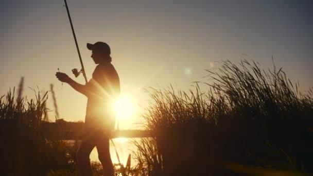 rybář rybaření ryba silueta na životní styl západu slunce. muž rekreace s rybářským prutem venkovní lov ryb při východu slunce. koníčky rybolov sportovní koncept západ slunce. muž relaxuje s rybářskou tyčí