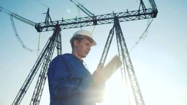 electrical engineer worker in helmet a working with digital tablet, near tower with electricity. business energy technology industry concept. electrician studying reading documents on lifestyle tablet