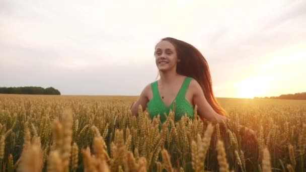 free girl run across the wheat field in the park. agriculture kid children dream concept. fun girl farmer hands to sides runs across the wheat field . happy free girl run in park agricultural land