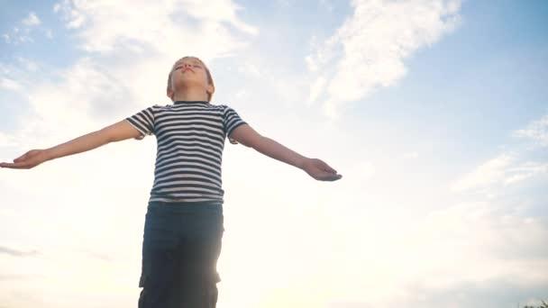 A fiú imádkozik, hogy felemelje a kezét az égre a kék égre. gyermek életmód fogalom hit vallás és boldog család. A fiú oldalra teszi a kezét a kék égi zsidó ellen, aki Istenhez imádkozik. imádat és hála