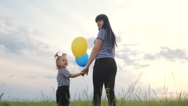 šťastná rodinná dcera a máma v parku s balónky silueta týmová práce narozeninová párty při západu slunce. Koncept společné šťastné rodiny. šťastná rodina dítě dívka batole drží ruku jeho