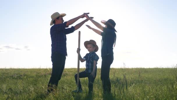 Die Silhouette des glücklichen Familienvaters Sohn und der Mutter zeigt ein Haus und ein Trostsymbol bei Sonnenuntergang. glückliche Familie Eltern Mutter und Vater und Kinder zeigen Hausdach halten ihre Hände über dem Kopf