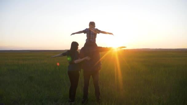 glückliche Familie kuschelnden Vater, Mutter und Sohn zeigen Flugzeug Hände spielen Superhelden Pilot Teamwork. Papa Mama legte seinen kleinen Sohn auf seinen Nackenschmusstand zurück zum Sonnenuntergang. glückliche Eltern und Kind der Familie