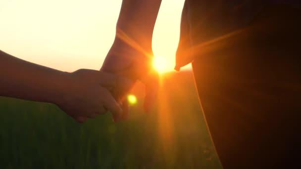 Glückliche Familienmütter und -söhne halten Händchen. Mutter und Junge Hand in Hand bei Sonnenuntergang. Eltern Mädchen und Lifestyle Kind glückliche Kindheit