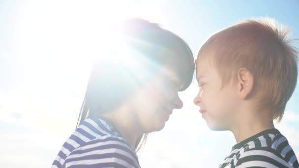 syn a máma roztomilé video koncert matky den. Týmová práce šťastný rodinný chlapec políbí matku na tvář dotýká se jeho nosu. rodič se o dítě stará. dítě a dospělá žena maminka v životním stylu sluneční světlo na