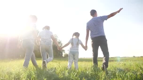 glückliche Familie beim Spaziergang im Park. freundliche Familien-Kind-Traum-Konzept. Mama Papa und Kinder spazieren im Park auf grünem Gras im Freien. glückliche Familie mit dem Rücken zu Fuß im Park in